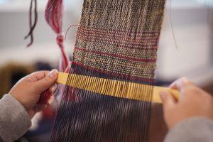 Volunteer weaving at flax workshop