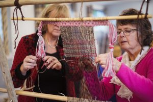 Volunteers weaving during flax workshop